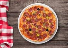 Pizza com opinião superior do salame na tabela de madeira Imagens de Stock