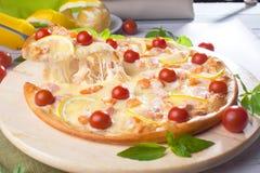 A pizza com os peixes vermelhos do marisco, salmões, camarão, tomates, ainda vida, queijo, estiramentos, ombro, fatia, aumenta Imagem de Stock Royalty Free