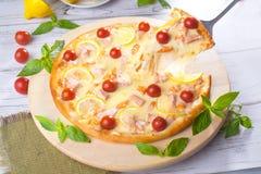 A pizza com os peixes vermelhos do marisco, salmões, camarão, tomates, ainda vida, queijo, estiramentos, ombro, fatia, aumenta Fotografia de Stock