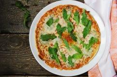Pizza com queijo e rúcula em uma placa Fotos de Stock Royalty Free