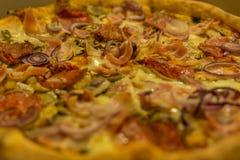 A pizza com salame, presunto, cebola, azeitonas, focalizou no moddle Fotografia de Stock Royalty Free