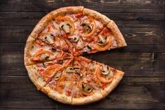 Pizza com salame, salmouras, tomates, queijo e presunto em um fundo de madeira escuro, vista superior Fotografia de Stock