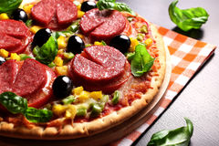 Pizza com tomate, salame, azeitonas e manjericão Imagens de Stock