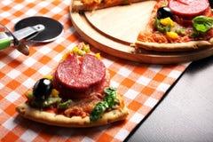 Pizza com tomate, salame, azeitonas e manjericão Foto de Stock