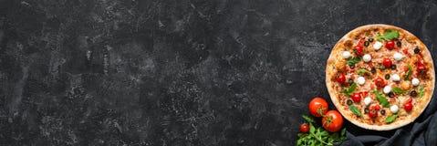 Pizza com tomates, mozzarella, rúcula e molho no fundo de pedra preto imagem de stock royalty free