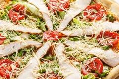 Pizza con bacon, le erbe ed i pomodori in un piatto bianco su un primo piano bianco del fondo fotografia stock