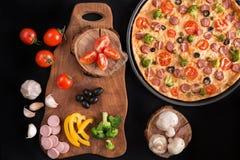 Pizza con bróculi, los guisantes, la salchicha, las aceitunas, las pimientas y los tomates Imágenes de archivo libres de regalías