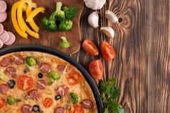 Pizza con bróculi, los guisantes, la salchicha, las aceitunas, las pimientas y los tomates Fotografía de archivo libre de regalías
