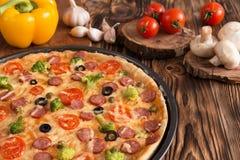 Pizza con bróculi, los guisantes, la salchicha, las aceitunas, las pimientas y los tomates Foto de archivo libre de regalías