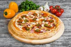 Pizza con carne affumicata, con i rosmarini e le spezie su un fondo di legno leggero fotografia stock
