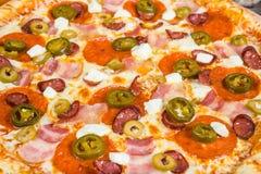 Pizza con carne affumicata, con i rosmarini e le spezie su un fondo di legno leggero fotografia stock libera da diritti
