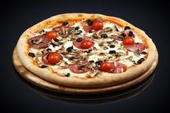 Pizza con carne assortita ed i pomodori fotografia stock