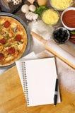 Pizza con el cuaderno, la tajadera y los ingredientes Foto de archivo libre de regalías