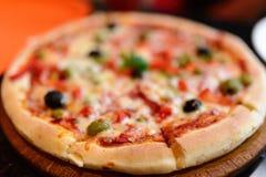 Pizza con el jamón, la pimienta y aceitunas fotos de archivo libres de regalías