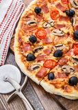 Pizza con el jamón, las setas y las aceitunas Imágenes de archivo libres de regalías