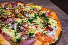 Pizza con el jamón y el queso en un tablero Imágenes de archivo libres de regalías