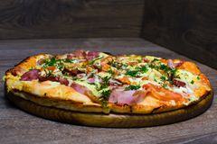 Pizza con el jamón y el queso en un tablero Imagen de archivo