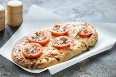 Pizza con el queso y los tomates, especias de las hierbas en un backg concreto Imagen de archivo libre de regalías
