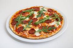 Pizza con el salami, el queso y el arugula Fotos de archivo libres de regalías