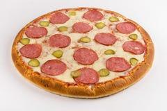 Pizza con el salami, el queso y el pepino en un fondo blanco fotos de archivo libres de regalías