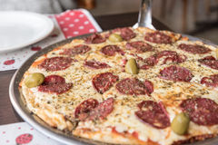Pizza con el salami y las aceitunas en el EL Calafate, la Argentina Imágenes de archivo libres de regalías