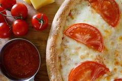 Pizza con el tomate en un tablero de madera Foto de archivo libre de regalías