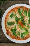 Pizza con formaggio e rucola su un piatto immagine stock libera da diritti