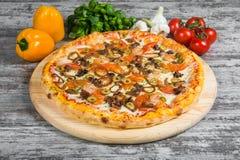 Pizza con frutti di mare, con i rosmarini e le spezie su un fondo di legno leggero fotografia stock libera da diritti