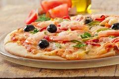Pizza con gamberetto, il salmone e le olive Immagini Stock