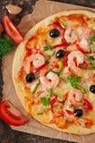 Pizza con gamberetto, il salmone e le olive Fotografia Stock