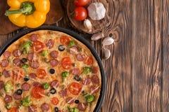 Pizza con i broccoli, i piselli, la salsiccia, le olive, i peperoni ed i pomodori Fotografie Stock