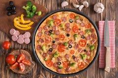 Pizza con i broccoli, i piselli, la salsiccia, le olive, i peperoni ed i pomodori Fotografie Stock Libere da Diritti
