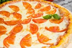 Pizza con i pomodori, con i rosmarini e le spezie su un fondo di legno leggero fotografie stock