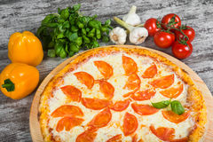 Pizza con i pomodori, con i rosmarini e le spezie su un fondo di legno leggero immagine stock libera da diritti