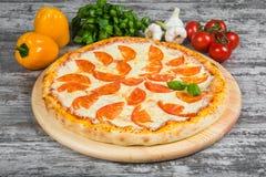 Pizza con i pomodori, con i rosmarini e le spezie su un fondo di legno leggero immagine stock