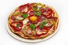 Pizza con i pomodori e la salsiccia e l'uovo del peperone dolce su un piatto immagine stock