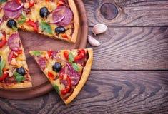 Pizza con il pomodoro, il salame e le olive Immagini Stock