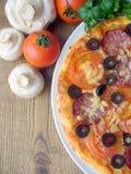 Pizza con il pomodoro, salsiccia, funghi, formaggio, oli Fotografie Stock