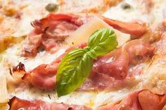 Pizza con il prosciutto al forno e il grana Immagini Stock Libere da Diritti
