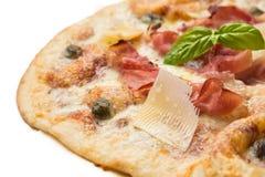 Pizza con il prosciutto al forno e il grana Fotografia Stock
