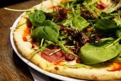 Pizza con il prosciutto e gli spinaci, fondo di legno, prodotti freschi, uff fotografia stock libera da diritti