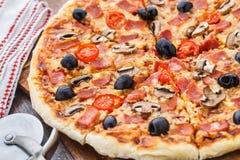Pizza con il prosciutto, i funghi e le olive Fotografie Stock Libere da Diritti
