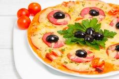 Pizza con il prosciutto, i pomodori e le olive selettivo Immagini Stock