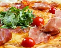 Pizza con il prosciutto, i pomodori ed i verdi Immagine Stock