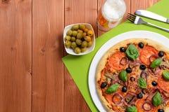 Pizza con il prosciutto, le olive ed i funghi Fotografie Stock