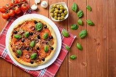 Pizza con il prosciutto, le olive ed i funghi Fotografia Stock