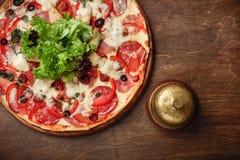 Pizza con il prosciutto, il salame, il formaggio, i funghi, i pomodori ciliegia, i peperoni dolci e l'insalata su un bordo marron immagine stock