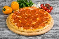 Pizza con il salame delle merguez con i rosmarini e le spezie su un fondo leggero fotografia stock