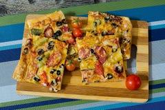 Pizza con la salchicha, las aceitunas, los tomates y el queso Fotos de archivo libres de regalías