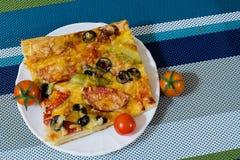 Pizza con la salchicha, las aceitunas, los tomates y el queso Imagen de archivo